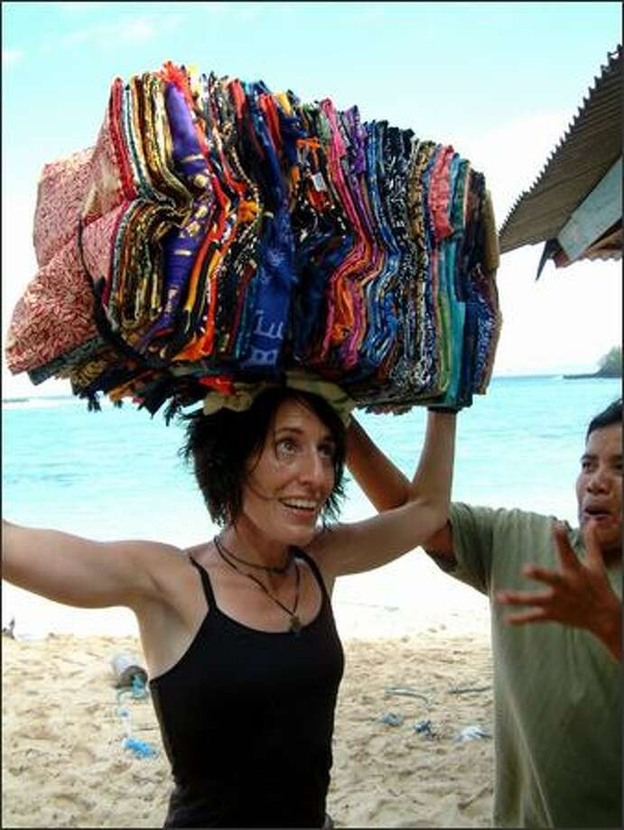 A sarong seller from the small southern Bali town of Padangbai tries to teach Winda (unsuccessfully) how to carry things on top of her head. For Indonesian women, carrying heavy loads atop their heads is no big deal. But give it a try and you'll soon find out it takes a whole lot of strength and balance. Photo: Richie Costleigh, Special To Seattle Post-Intelligencer / Special to Seattle Post-Intelligencer