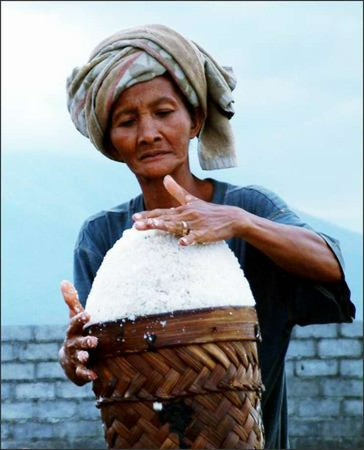 A woman packs salt into a basket at the end of the day. In the seaside village of Amed on the eastern coast of Bali, most of the residents make their living off the sea. Here, fishing and transforming ocean water into salt are primary sources of income. Making salt is a multi-part process that involves drying ocean water in long wooden troughs until the water evaporates and the salt crystals are left behind. Photo: Winda Benedetti, Special To Seattle Post-Intelligencer / Special to Seattle Post-Intelligencer