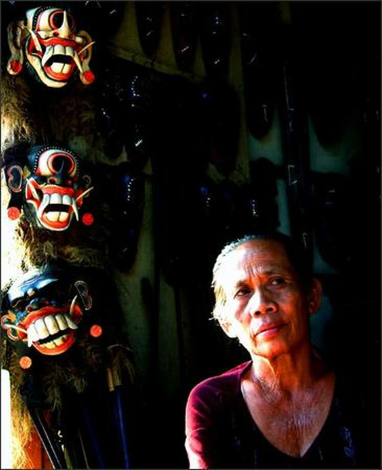 """A Balinese woman sells carved masks in Ubud. Regarded as the """"cultural capital"""" of Bali, Ubud is a relaxed town surrounded by rice fields and a good place to see Balinese dance and theatrical performances. Photo: Winda Benedetti, Special To Seattle Post-Intelligencer / Special to Seattle Post-Intelligencer"""