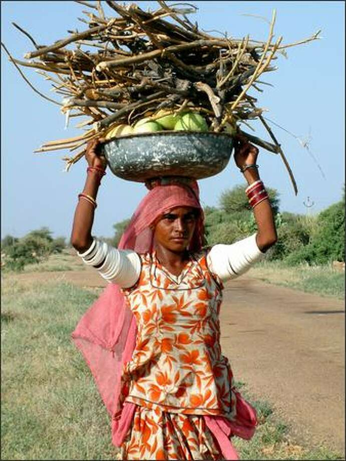 A woman carries a heavy load on top of her head in the hot afternoon sun. Whether they were working in the farm fields, scrubbing the family laundry by hand in a nearby river or carrying loads of firewood to cook dinner, the women of Indian seemed always to show a remarkable strength. Photo: Winda Benedetti, Special To Seattle Post-Intelligencer / Special to Seattle Post-Intelligencer