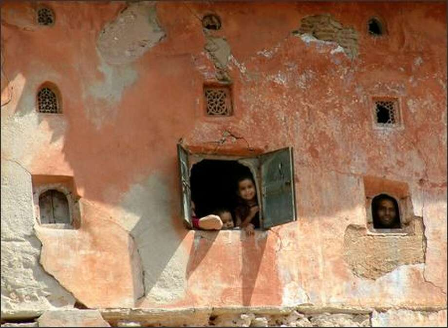 """From the worn windows of a Jaipur building residents watch the wacky tourist take pictures. Jaipur is the capital of Rajasthan and known as the """"the pink city."""" Photo: Winda Benedetti, Special To Seattle Post-Intelligencer / Special to Seattle Post-Intelligencer"""