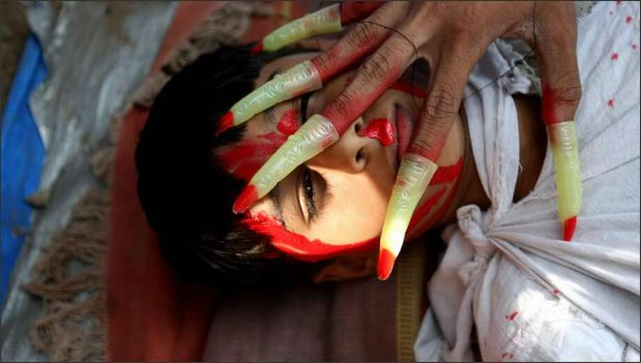 "An Indian child, his face covered with red paint to resemble blood, lies on the ground as a man dressed as a ghost ""attacks"" him as they protests against Israel's military operations in Gaza during a demonstration in Mumbai on Thursday. Photo: Getty Images / Getty Images"