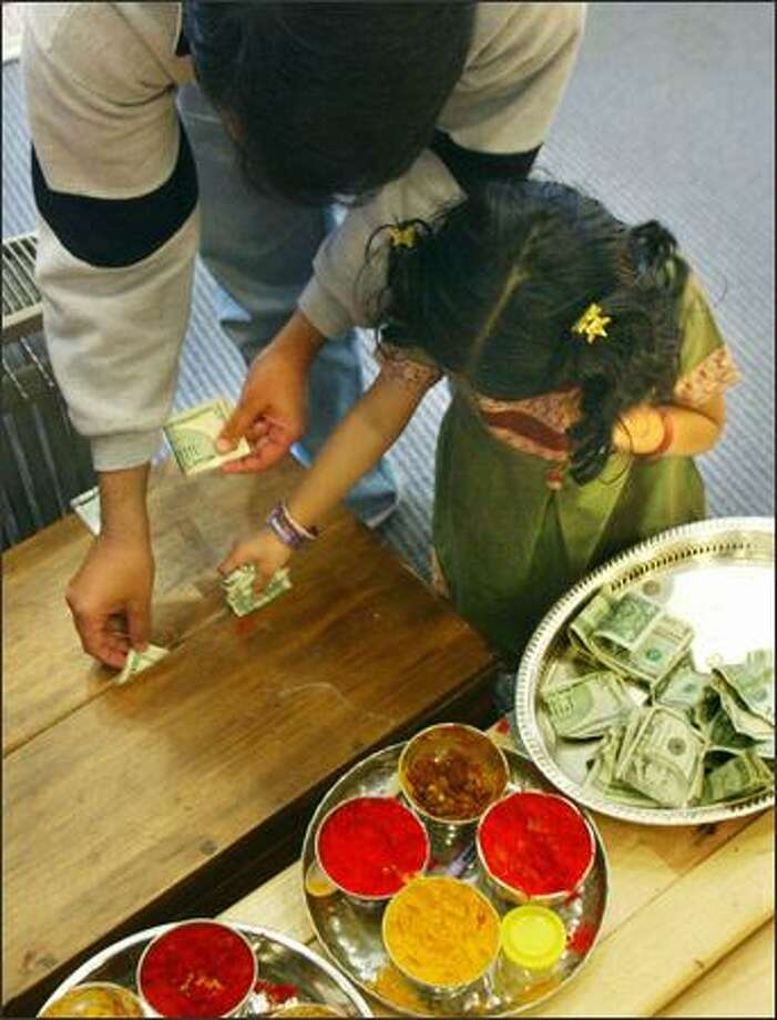 Vinay Haria, left, helps his daughter Smriti Haria, 4, both from Federal Way, put money collected for the Hindu Temple and Cultural Center in Bothell into a collection box at the end of a service which remembered victims of the tsunami in Asia. Photo: Karen Ducey, Seattle Post-Intelligencer / Seattle Post-Intelligencer