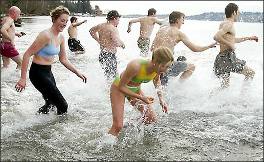 Just after noon Tuesday, about 30 students, staff and faculty from Bastyr University in Kenmore braved the chilly waters of Lake Washington as part of the school's 6-year-old traditional Splash and Dash. Student Kristin Foreman, center, stops to pick up a rubber duck on the way in, winning a couple of pairs of HotHands hand warmers. Photo: Gilbert W. Arias, Seattle Post-Intelligencer / Seattle Post-Intelligencer