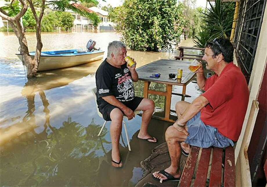Bar hopping by boat: Tens of thousands of people in Rockhampton, Australia, face isolation after floodwaters closed the city's airport, railway and roads. But if you have a boat, you can still get a frosty one at the Pioneer Hotel, as Cowboy Burnett (left) and Moose Malone demonstrate. Photo: Torsten Blackwood, AFP / Getty Images / AFP / Getty Images