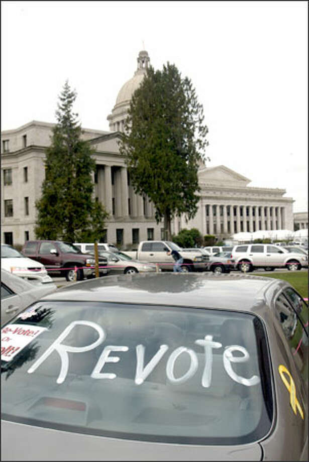 A sign painted in the window of a car on the Capitol grounds in Olympia expresses an opinion about the governor's race, which lawmakers are debating. Photo: Mike Urban, Seattle Post-Intelligencer / Seattle Post-Intelligencer