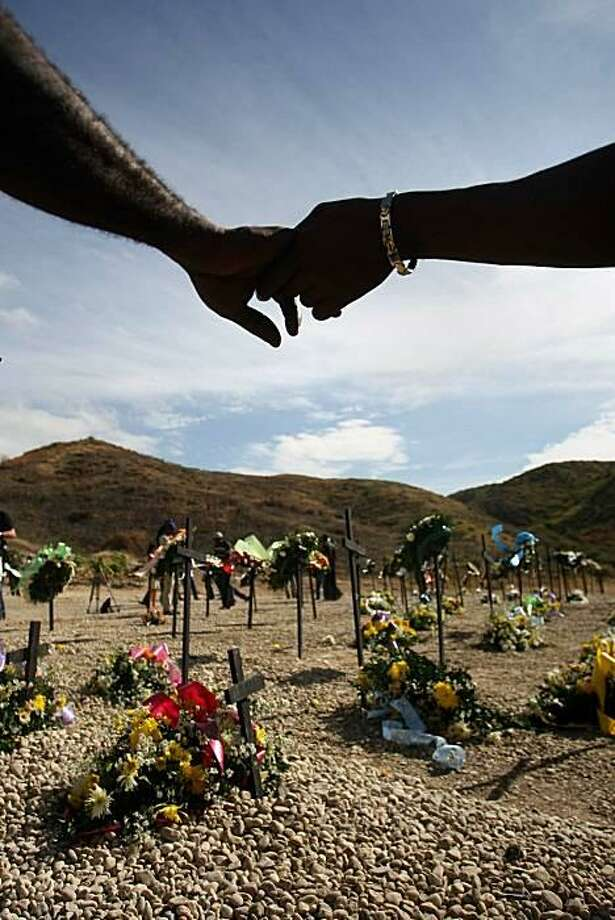 Haitians hold handsduring a ceremony at St. Christophe, Port-au-Prince, where thousands of victims of the Jan. 12, 2010, earthquake are buried. Haiti began two days of remembrance ceremonies in honor of the nearly quarter million people who died in the quake. Photo: Hector Retamal, AFP / Getty Images / AFP / Getty Images