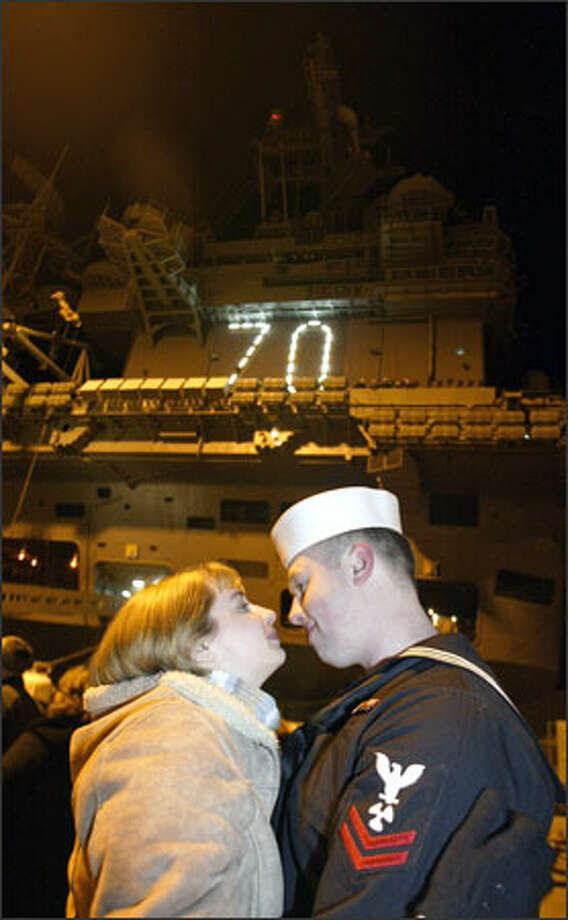 Susan Higbe gazes into the eyes of her husband of 15 months, Petty Officer 2nd Class Joe Higbe, before he boards the USS Carl Vinson. Higbe was among sailors who left Bremerton Thursday for a six-month, round-the-world cruise that will end in Norfolk, Va. Photo: Jim Bryant, Seattle Post-Intelligencer / Seattle Post-Intelligencer