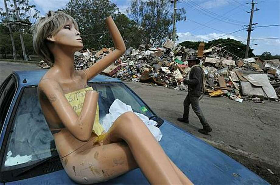 A mannequin sits on a car hood next to a pile of debris removed from a flood-damaged house in the Brisbane suburb of Fairfield. An army of volunteers turned out to clean up Australia's third-largest city after epic floods. Photo: Mark Ralston, AFP / Getty Images / AFP / Getty Images