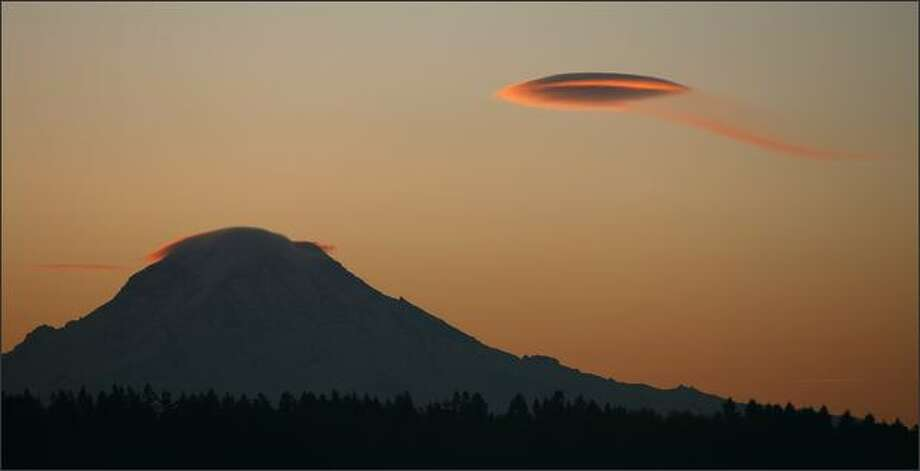 "It appears a UFO is flying over the southern slopes of Mount Rainier early Tuesday morning. But the ""craft,"" sporting an orange racing stripe and wispy condensation trail, is actually a small lenticular cloud, commonly formed when damp winds pass over the crest of high obstacles, such as mountains. Photo: Mike Urban, Seattle Post-Intelligencer / Seattle Post-Intelligencer"