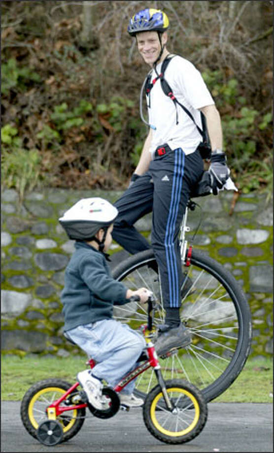 "Jeff Sloan, aboard his 36-inch Coker commuting unicycle, passes 4-year-old Jackson Higuere while riding along the waterside pathway at Lincoln Park in West Seattle. ""A bicycle is just a unicycle with a training wheel,"" Sloan told Jackson, who said he wants a unicycle when he gets bigger. The large-diameter wheel allows the cycle to travel farther with each pedal stroke. Photo: Mike Urban, Seattle Post-Intelligencer / Seattle Post-Intelligencer"
