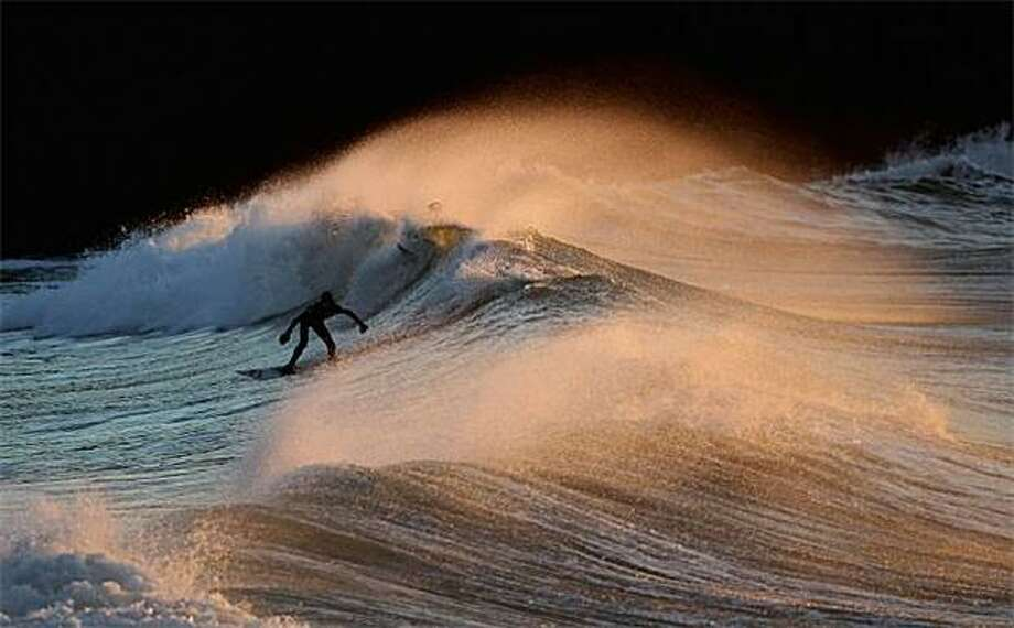 Catch a wave, catch a cold:A surfer braves the frigid swells off Polzeath, England. Photo: Matt Cardy, Getty Images / Getty Images