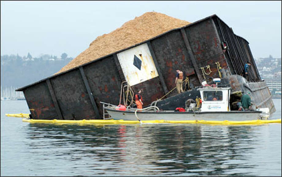 A barge containing wood chips lists in Puget Sound after taking water two miles southwest of Shilshole Bay in Seattle.  According to the U.S. Coast Guard, the tug Emma Foss was tending to the barge and reported no injuries or pollution. A precautionary boom was deployed. Photo: Fred Felleman, Special To The Seattle Post-Intelligencer / Special to the Seattle Post-Intelligencer