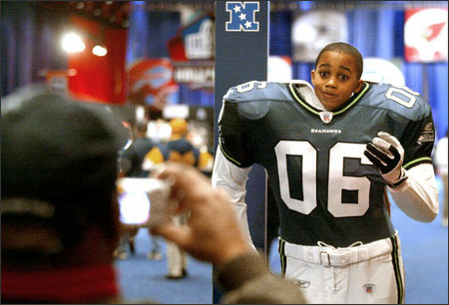 Nine-year-old Anthony Green of Detroit peers out from inside a life-sized Seattle Seahawks player replica at the interactive NFL Experience display at Detroit's Cobo Center. Green was a resident of Kirkland before his family moved to Detroit. Photo: Scott Eklund, Seattle Post-Intelligencer / Seattle Post-Intelligencer