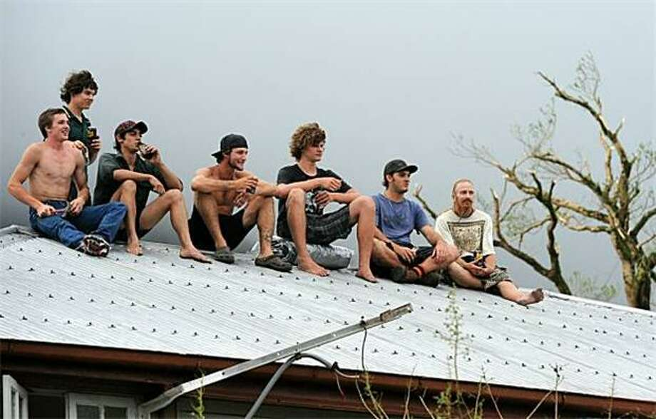 A house with seven lightning rods:In Tully, Queensland, mates drinking cans of rum and cola sit on a metallic roof as they watch an approaching thunderstorm in the aftermath of Cyclone Yasi. Australia's worst cyclone in a century devastated towns and left 175,000 people without power, but miraculously no deaths were reported. Photo: Torsten Blackwood, AFP / Getty Images / AFP / Getty Images