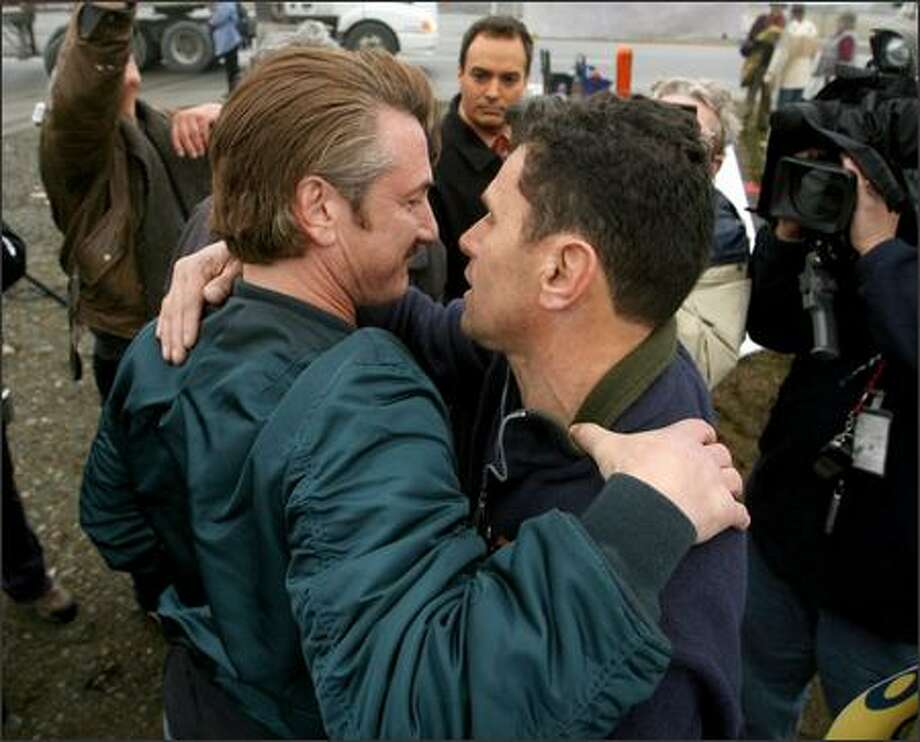 Actor Sean Penn, left, hugs Carlos Arredondo, whose son, Alex Arredondo, was killed in Iraq, near the entrance for Fort Lewis, during a rally in support of Lt. Ehren Watada. Photo: Scott Eklund, Seattle Post-Intelligencer / Seattle Post-Intelligencer
