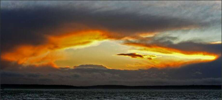 At the end of a stormy Seattle day a brilliant sunset makes an orange halo as it filters through the clouds over Puget Sound as seen from the Seattle waterfront. Photo: Gilbert W. Arias, Seattle Post-Intelligencer / Seattle Post-Intelligencer