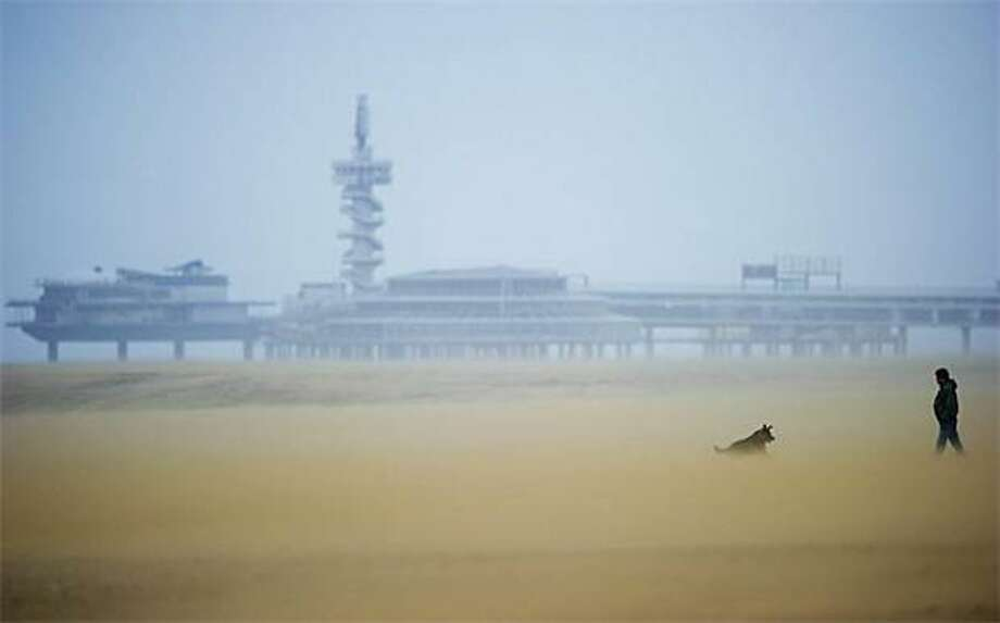 Grit happens: A man walks his dog in 60-mph winds on a beach in Scheveningen, Netherlands. Photo: Robin Utrecht, AFP / Getty Images / AFP / Getty Images