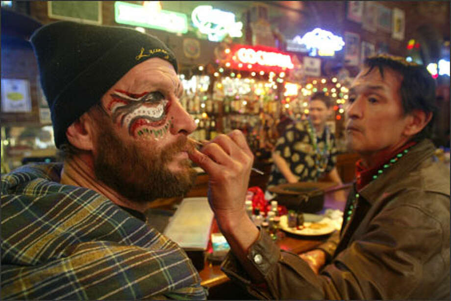 Bruce Berry of Seattle has his face painted by artist Ron Hilbert at the bar in Pioneer Square's New Orleans Creole Restaurant yesterday during the Mardi Gras celebration. Photo: Mike Urban, Seattle Post-Intelligencer / Seattle Post-Intelligencer