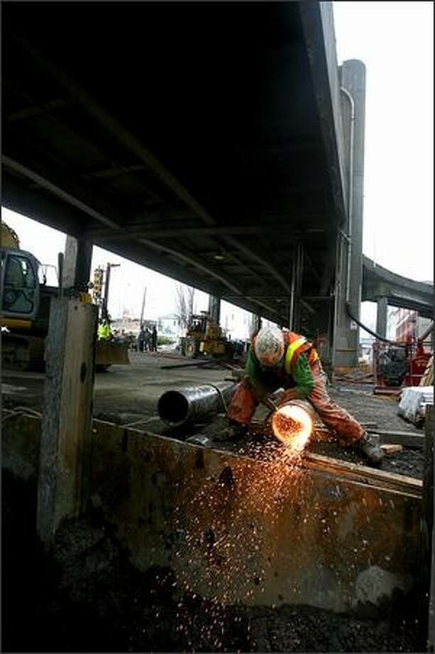 Doug Woods uses an oxy acetylene cutting torch as he cuts off the bottom of one of the temorary support columns that will be used to stablelize the viaduct during construction. Crews, during the weekend, began installing temporary support structures below the lower deck of the Alaskan Way viaduct between Columbia Street and Yesler Way. Photo: Scott Eklund, Seattle Post-Intelligencer / Seattle Post-Intelligencer