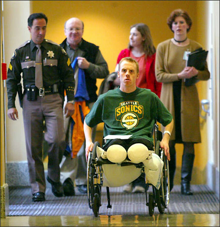 Backcountry skier Dan Witkowski, 25, wheels himself down a corridor at Harborview Medical Center to meet and talk with reporters. Witkowski left Harborview for his Ellensburg home six days after he underwent surgery to amputate both legs below his knees. He spent four nights in January lost in snow near Snoqualmie Pass, suffering frostbite to his feet and hands. His hands are healing, and Witkowski says he will be back on the slopes again. Witkowski's father, Robert, and his sister, Elizabeth, are behind him at center. Photo: Grant M. Haller, Seattle Post-Intelligencer / Seattle Post-Intelligencer