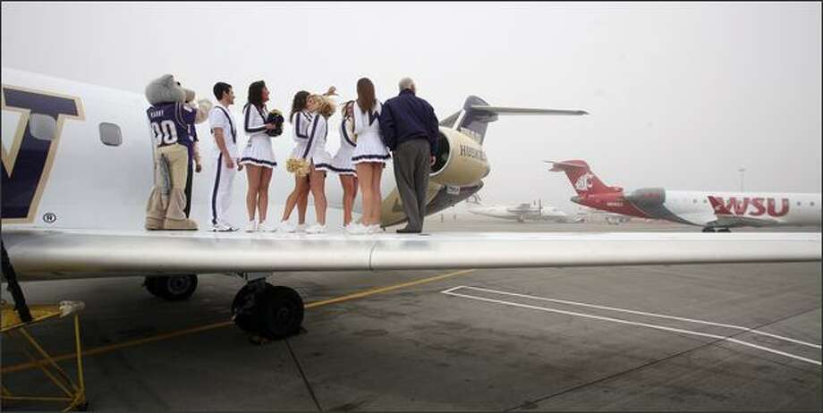 The best-laid plans of the University of Washington Alumni Association and Huskies cheerleaders were somewhat upstaged Tuesday at Gate 3B at Seat-Tac Airport. Horizon Air has painted four Bombardier CRJ-700 jets with the colors and logos of the UW, the University of Oregon, Oregon State University and the Huskies' archrival, Washington State University. The UW invited the media to record the Huskies cheerleaders on the wing of their newly painted jet, while concidentaly, the jet painted in WSU colors was towed from a nearby gate before its scheduled departure for Fresno, Calif. The distraction was unappreciated on the wing of the Huskies' plane. Photo: Paul Joseph Brown, Seattle Post-Intelligencer / Seattle Post-Intelligencer