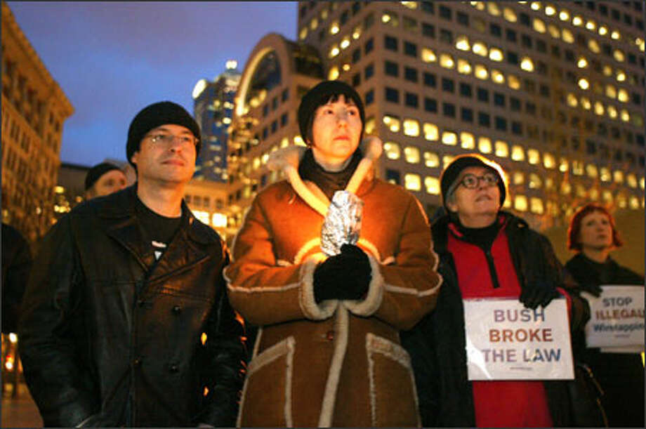 "From left, Larry Golding, Terisa Greenan and Janice Winchester join others Wednesday night during a candlelight ""Constitution Vigil"" at Westlake Plaza in downtown Seattle. Photo: Gilbert W. Arias, Seattle Post-Intelligencer / Seattle P-I"