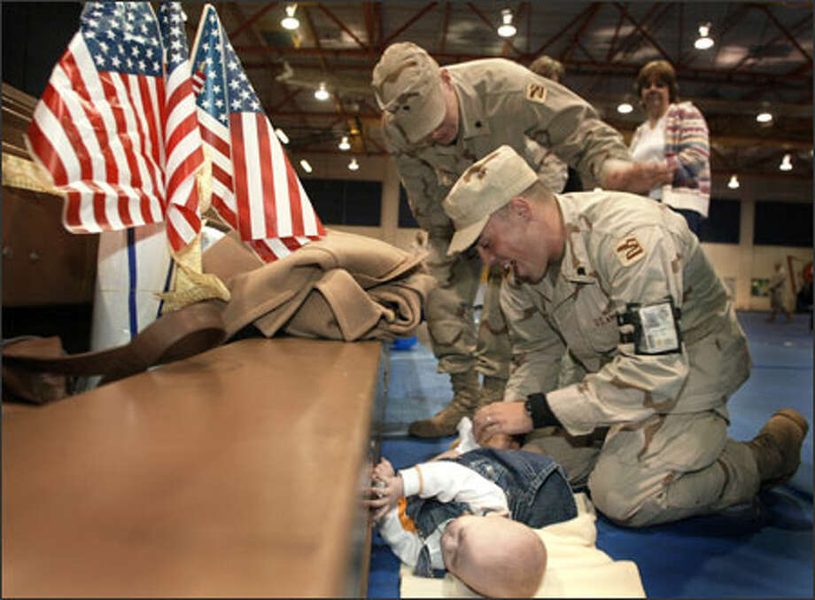 Spc. Ryan Allen of the Washington National Guard changes the diaper on his son, Noah, after his unit's welcome-home ceremony at Fort Lewis. Photo: Joshua Trujillo, Seattlepi.com / Seattle Post-Intelligencer