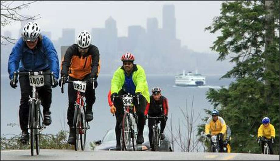A state ferry heading toward Seattle provides the backdrop for riders participating in the annual Chilly Hilly bike ride on Bainbridge Island Sunday. Photo: Dan DeLong, Seattle Post-Intelligencer / Seattle Post-Intelligencer