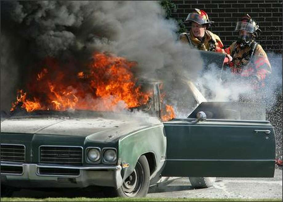 Lt. Kory Custer, left, and firefighter Cathy Browning of Tukwila Fire Department Engine 51 battle a car fire Monday at Southcenter Mall. An apparent wire short started the blaze, which spread to a pickup parked nearby. Photo: Mike Urban, Seattle Post-Intelligencer / Seattle Post-Intelligencer