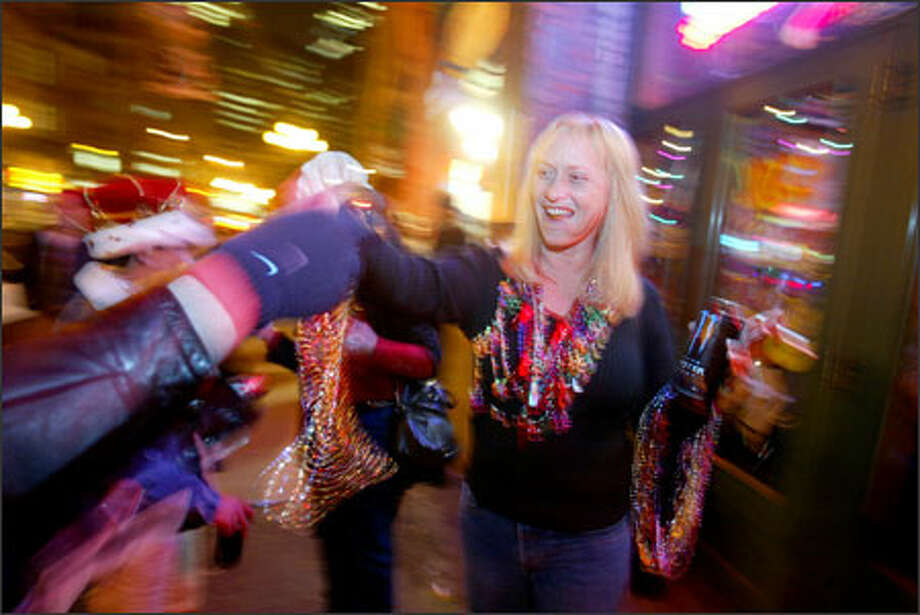 Audrey Peters hands out beads in front of the New Orleans restaurant in Pioneer Square on Fat Tuesday. Photo: Scott Eklund, Seattle Post-Intelligencer / Seattle Post-Intelligencer