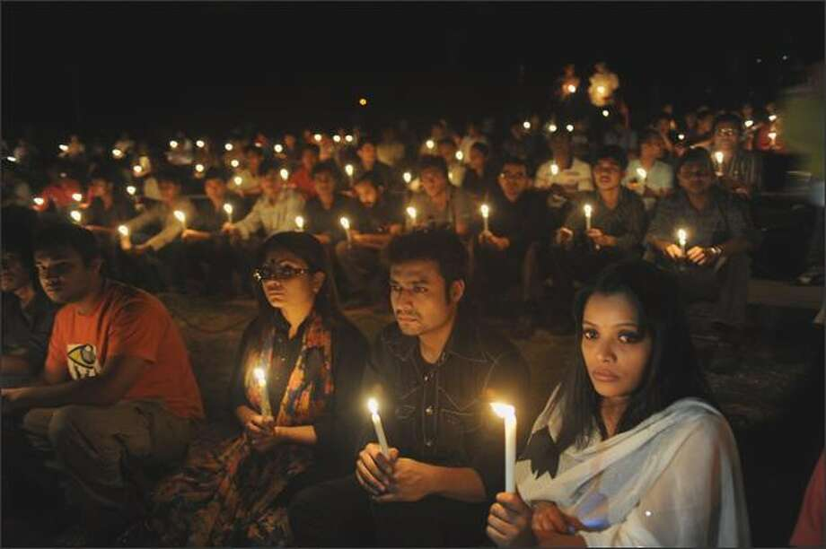 Bangladeshi citizens hold Sunday candles during a remembrance gathering for people killed during the recent mutiny at the Bangaldesh Rifles heaquarters in Dhaka. Bangladeshi police were hunting for more than 1,000 troops accused of murder during a bloody mutiny in which 77 people have so far been confirmed dead. Photo: Getty Images / Getty Images
