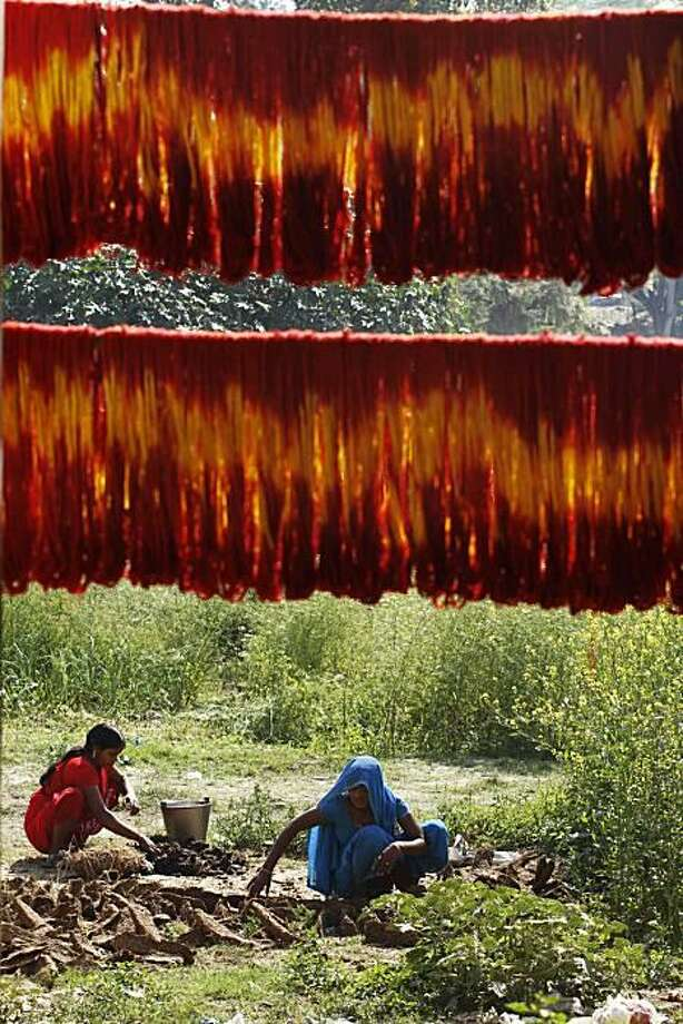 Easy-bake cow pies: Threads dyed brilliant hues for use in Hindu rituals dry in the sun as women make dung cakes in the village of Lalgopalgunj, India. Photo: Rajesh Kumar Singh, AP / AP