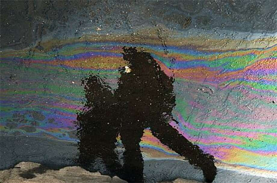 Oil and water:A petroleum film on wet asphalt reflects passing pedestrians in Bucharest. Photo: Daniel Mihailescu, AFP / Getty Images / AFP / Getty Images