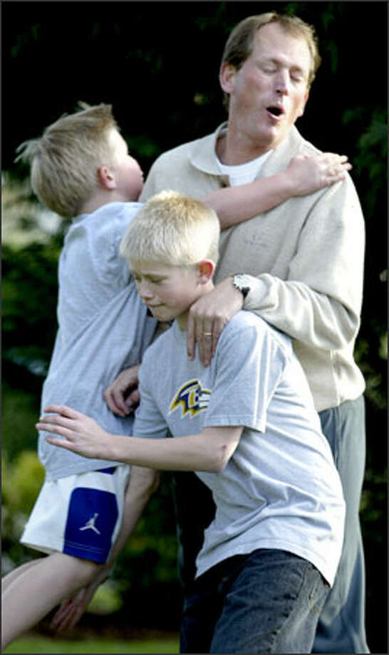 Rick Neuheisel is sacked by his son Joe, 8, as son Jerry, 12, defends the new quarterbacks coach of the NFL's Baltimore Ravens while they play front-yard football at their home in Medina. Photo: Mike Urban, Seattle Post-Intelligencer / Seattle Post-Intelligencer