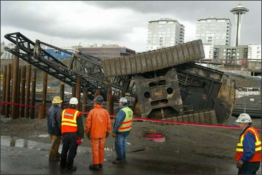 Workers examine a crane that tipped over Tuesday at the site of the Seattle Art Museum's Olympic Sculpture Park between Broad Street and Myrtle Edwards Park in Seattle. No injuries were reported when the crane fell across railroad tracks that run along the waterfront. Photo: Joshua Trujillo, Seattlepi.com / seattlepi.com