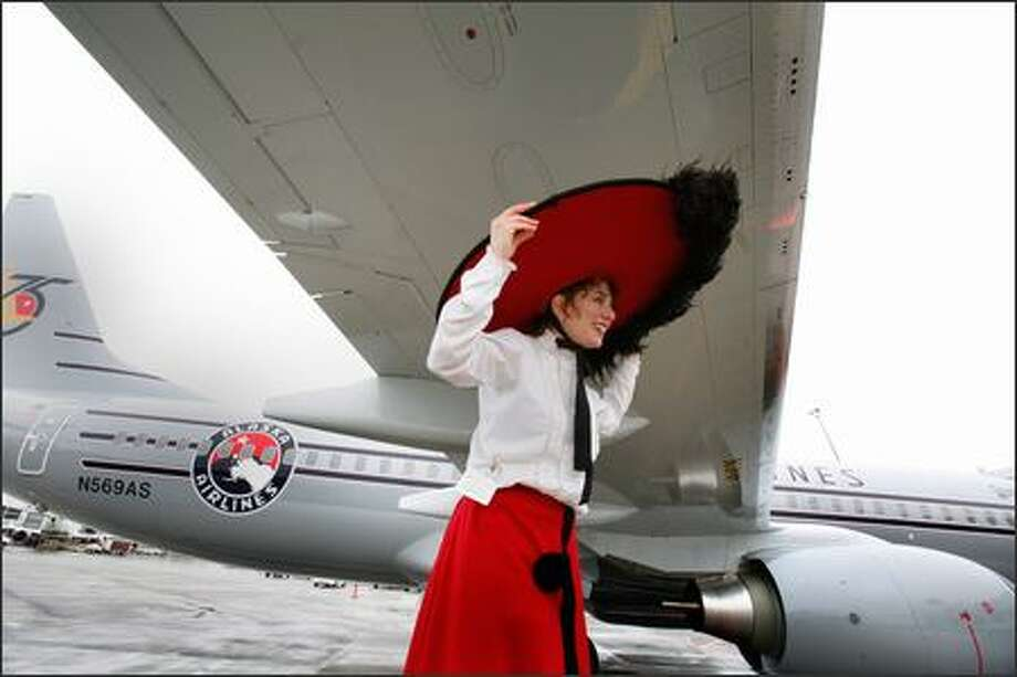 Janet Rayor, on stilts and in a Gay '90s uniform, helps unveil Starliner 75, a new Boeing 737-800 featuring the 1940s paint scheme, to celebrate Alaska Airlines' 75th anniversary Wednesday at Sea-Tac Airport. After the unveiling, the aircraft made its inaugural flight to Anchorage, Alaska, where the company began. Photo: Meryl Schenker, Seattle Post-Intelligencer / Seattle Post-Intelligencer