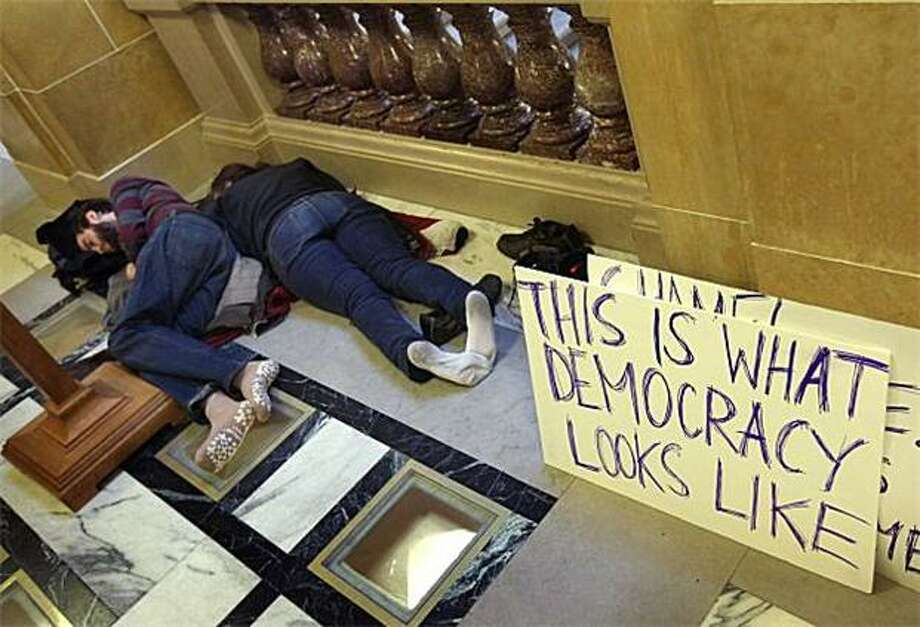 Democracy is totally exhausted:Protesters sleep in the Wisconsin State Capitol in Madison after Republican senators outmaneuvered their missing Democratic colleagues and voted to curb collective bargaining rights for state workers. The measure swiftly advanced to GOP Gov. Scott Walker, who promised to waste no time signing it. Photo: Scott Olson, Getty Images / Getty Images