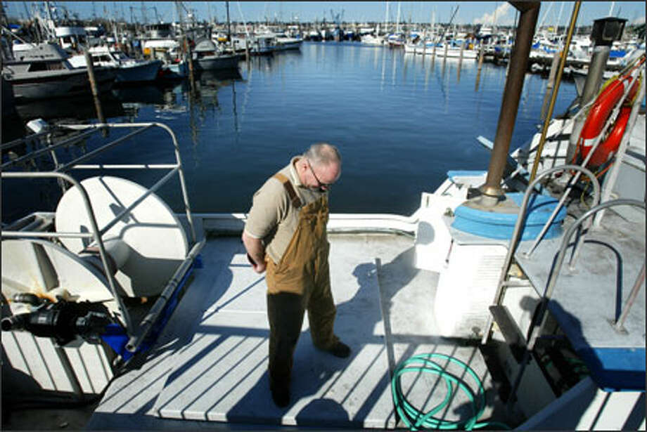 Fisherman John McDonald prays aboard his fishing boat Sanjo on Sunday at Seattle's Fishermen's Terminal before receiving a fleet blessing in the terminal's 77th annual event. Photo: Paul Joseph Brown, Seattle Post-Intelligencer / Seattle Post-Intelligencer