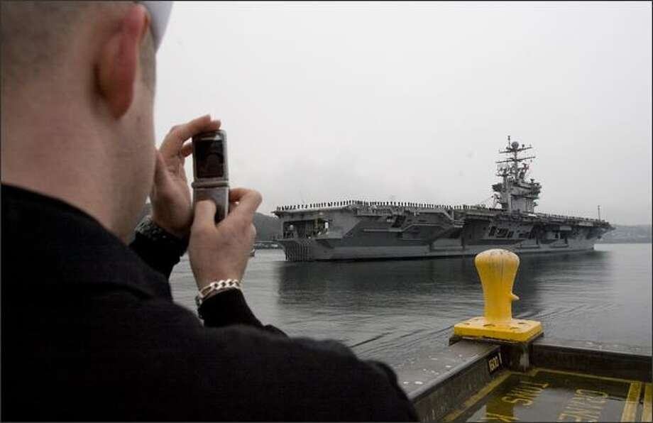 A sailor uses his cell phone Thursday to photograph the aircraft carrier USS Abraham Lincoln leaving Naval Station Everett for deployment to the western Pacific for seven months. The Lincoln will go to San Diego before heading to Iraq and Afghanistan. Photo: Grant M. Haller, Seattle Post-Intelligencer / Seattle Post-Intelligencer