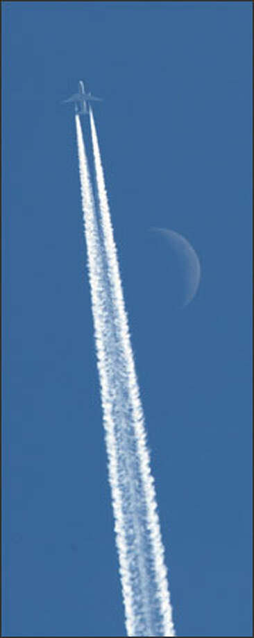 With a faint moon above, a jet leaves its contrail across another brilliant blue sky over Western Washington. Photo: Gilbert W. Arias, Seattle Post-Intelligencer / Seattle Post-Intelligencer