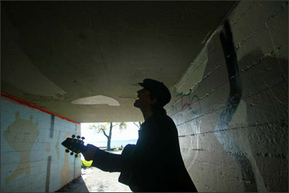 """Sloan Armitage of Ballard warms up for rehearsal Tuesday in the tunnel between parking lots at Golden Gardens Park. Armitage is a member of the band M Blue, which plays alternative rock that he calls """"views with blues."""" He likes to practice in the tunnel because there's a lot of echo, and """"I can hear the music come back at me."""" Photo: Karen Ducey, Seattle Post-Intelligencer / Seattle Post-Intelligencer"""
