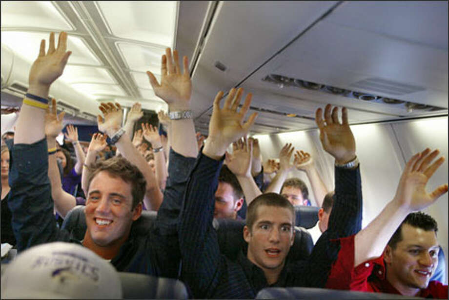 "University of Washington cheerleaders (l-r)  Seth Gililland, Christoff Elster and Joseph Vodegel raise their hands as the plane carrying the Husky cheer squad and marching band takes off for Boise, Idaho, for the NCAA basketball tournament. The squad performs this ritual, which includes singing the school fight son ""Bow Down to Washington,"" whenever it travels. Photo: Meryl Schenker, Seattle Post-Intelligencer / Seattle Post-Intelligencer"