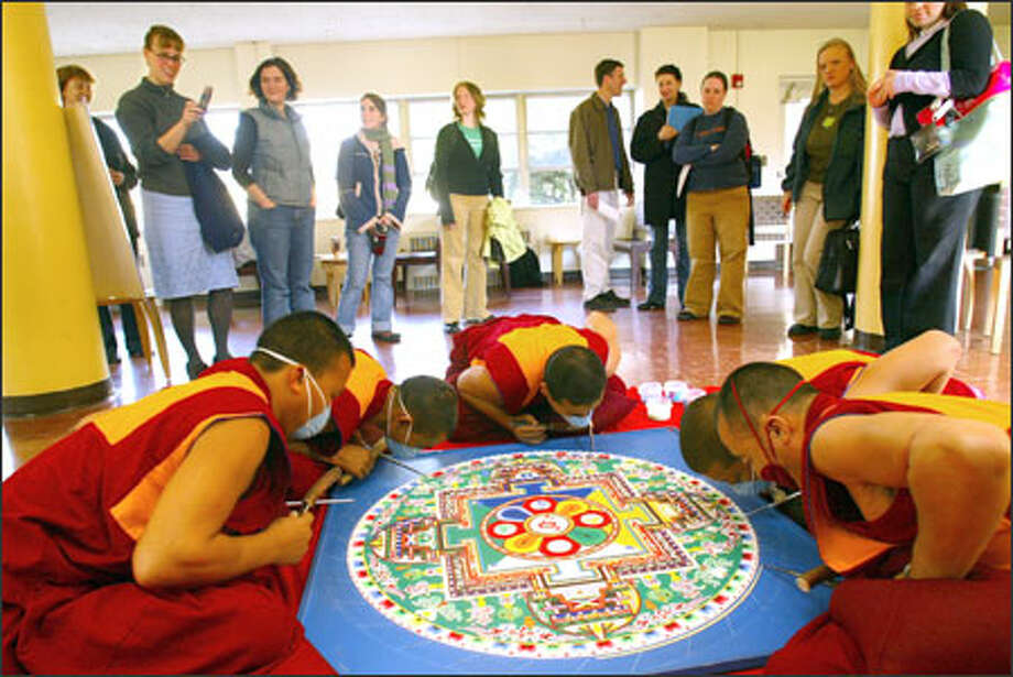 Students watch five of the 10 Tibetan monks from the Gaden Jangtse Monastery in southern India as they create a sand mandala of Chenrezig, the Buddha of Compassion, at Bastyr University in Kenmore.  Made of colored grains of sand, one grain at a time, the three-day process is a meditative exercise that honors impermanence.  The mandala is destroyed upon its completion, providing a lesson about the transitory nature of all existence. Photo: Grant M. Haller, Seattle Post-Intelligencer / Seattle Post-Intelligencer