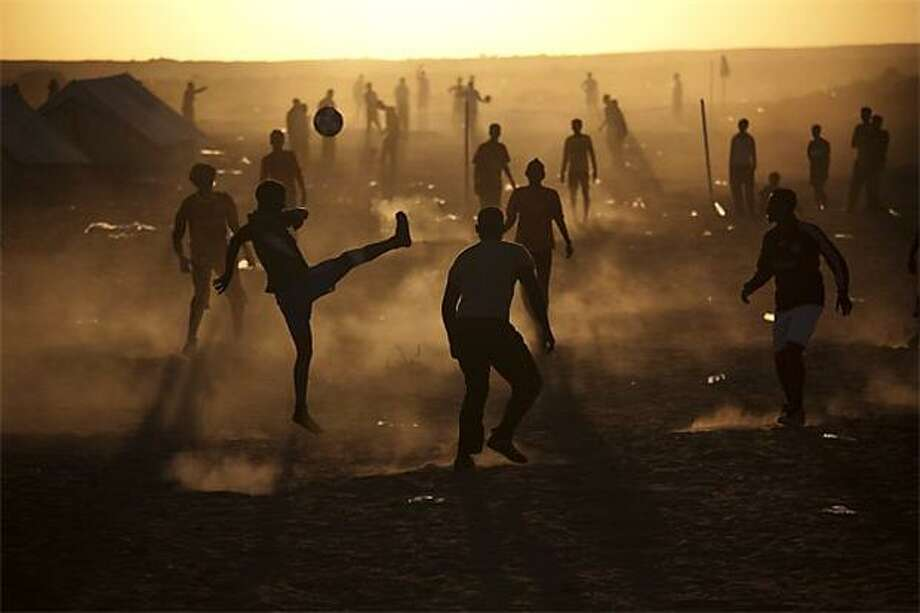 On a dusty pitch in a Tunisia-Libyan border camp, migrant workers-turned-refugees play football. They used to work in Libya but fled the conflict between rebel and regime forces. Photo: Emilio Morenatti, AP / AP