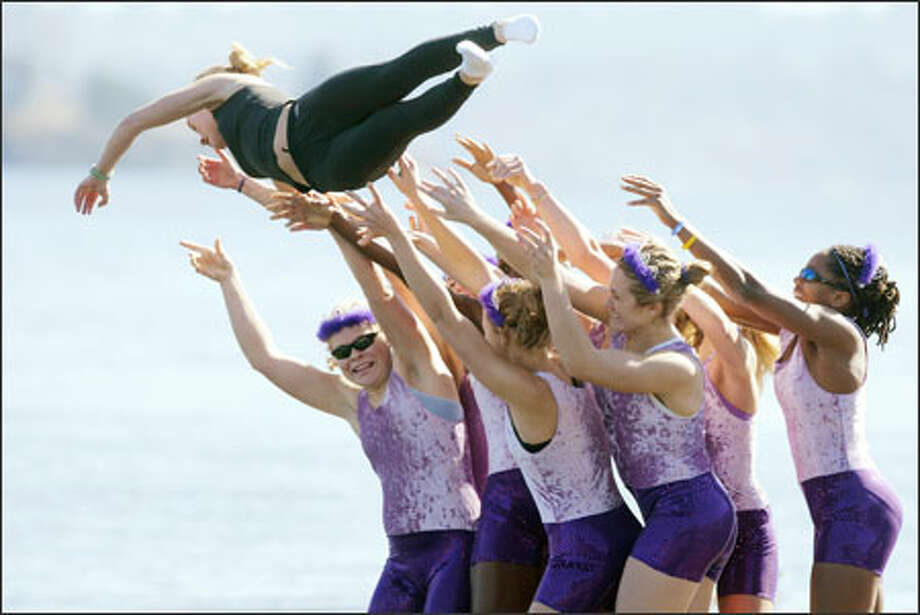 Crew members toss coxswain Laura Holcomb into the cold waters of Lake Washington after the juniors beat the seniors Sunday in the annual University of Washington Class Day Regatta. The race pits classes against each other for a prized pin, which the freshman men picked up for the first time in 59 years. Photo: Paul Joseph Brown, Seattle Post-Intelligencer / Seattle Post-Intelligencer