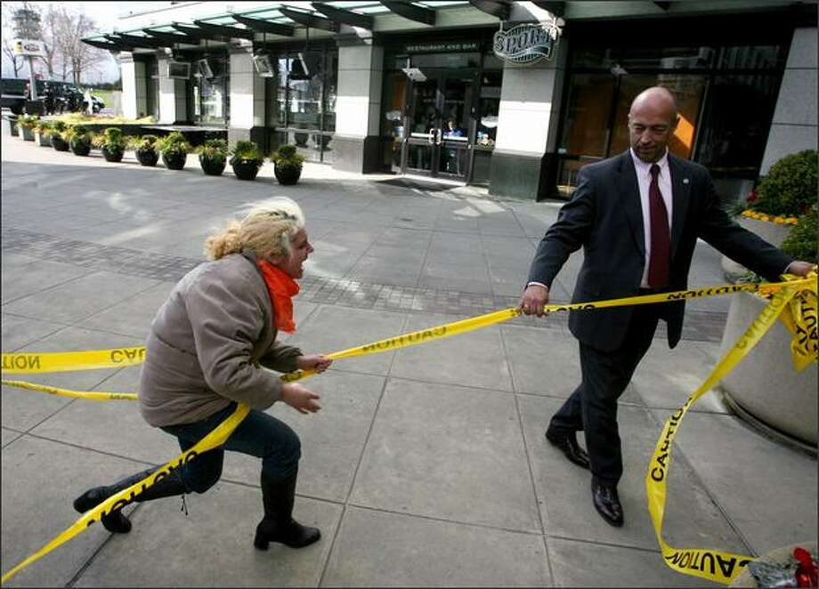 "Anti-war protester Emma Kaplan, (left) of Seattle, plays tug-of-war with an emplyee of Fisher Plaza with caution tape that anti-war protesters had wrapped around the building. The employee was removing it when Kaplan tried to pull it away from him. Kaplan said they put the tape up because, ""We put up this caution tape because we think this building is a crime scene. This media center is with war crimes and crimes against humanity and for not reporting the truth."" Protesters gathered at Fisher Plaza to protest the war in Iraq on the fifth year of its start. Protesters were there to protest what they said was a lack of media to report the war accurately and completely. About 40-50 people showed up to the protest on Wednesday, March 19, 2008 in Seattle. Photo: Scott Eklund, Seattle Post-Intelligencer / Seattle Post-Intelligencer"