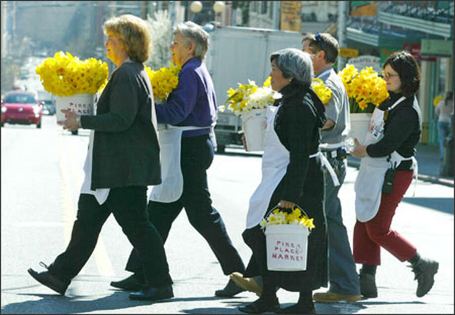 Volunteers from Pike Place Market crossed First Avenue Monday carrying some of the 13,000 daffodils donated by Market farmers and distributed around downtown Seattle in a cheerful celebration of the first day of spring. Photo: Paul Joseph Brown, Seattle Post-Intelligencer / Seattle Post-Intelligencer