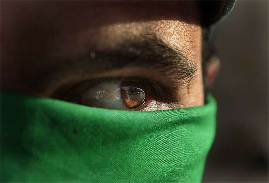 The empire strikes back: A pro-Gadhafi supporter hides his face behind a green scarf in Tripoli. Libyan government tanks and rockets pounded rebel forces into a panicked full retreat after an hours-long, back-and-forth battle. Photo: Jerome Delay, AP / AP