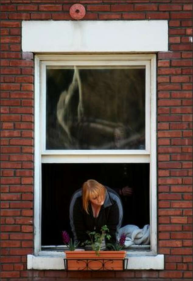 A resident of the Ascona Building watches the action below after an apparently intoxicated driver, who many witnesses said could barely stand and had a bottle of booze, drove across South Washington Street, hit a parked car and sent it into the Ascona Apartment building on 5th Avenue South in downtown Seattle. The car was braced with wood, ropes and straps. Eventually it was removed with a small crane on the back of a tow truck. Photo: Joshua Trujillo, Seattlepi.com / seattlepi.com
